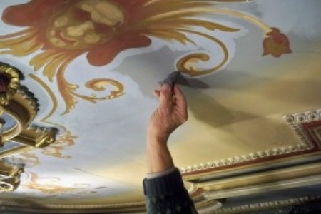 Conservator cleaning drawing room ceiling